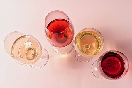 Flat lay. A set of rose and white wine in a glasses on pink background, toned in pink.