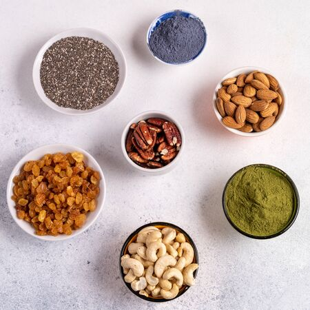 Collection of Superfoods and nuts in Bowls for health, fitness and vitality used for preparing energy balls. Top view. Gray concrete background.