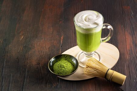 Matcha latte with cream foam in glasses, bamboo whisk tusaku and matcha powder on wood table.