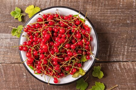 fresh ripe red currants in a bowl on an old wooden table, top view. Banque d'images