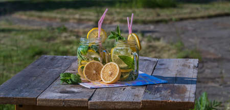 Homemade Lemonade with lemon, mint and ice in glass mugs on old wooden table, outdoor, spring. Zdjęcie Seryjne