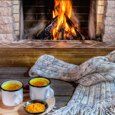 Golden latte milk in mugs with turmeric and spices before cozy fireplace. Healthy beverage.