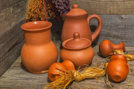 Still life with clay jugs of various sizes and bundles of dried medicinal herbs on an old wooden table.