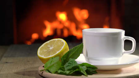 Cozy Fireplace and white cup of Tea with lemon and mint on a board before fireplace.