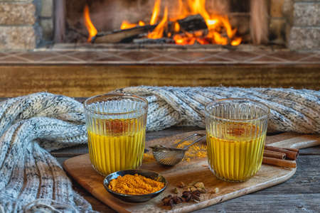Golden latte milk in glasses with turmeric and spices before cozy fireplace.