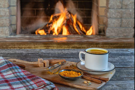 Golden latte milk made with turmeric and spices before cozy fireplace. Healthy beverage.