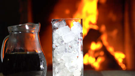 Coffee in a jar and Glass of ice in front of burning fireplace.
