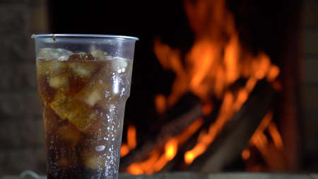 Plastic Glass of cola with ice in front of a burning fireplace in country house. Foto de archivo