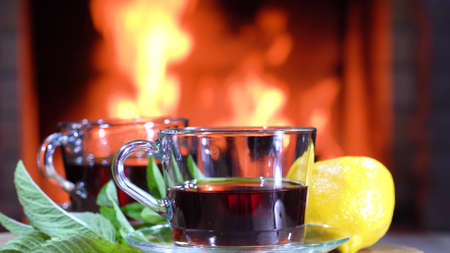 Glass cups of hot Tea with lemon and mint on a table before fireplace in a country house. Foto de archivo