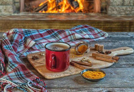 Golden latte milk in a red mug with turmeric and spices before cozy fireplace. Healthy beverage.