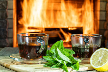 Cozy fireplace, glass cups of hot Tea with lemon and mint on table in a country house.