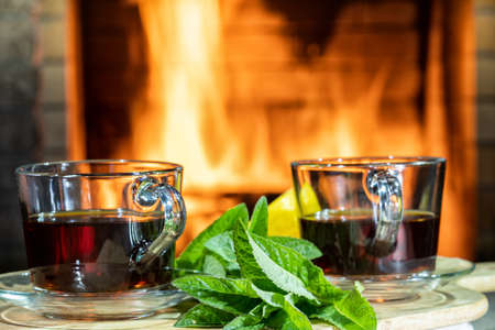 Cozy fireplace, glass cups of hot Tea with lemon and mint on a table in a country house. Foto de archivo