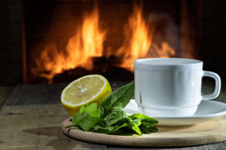 Burning Fireplace and cup of Tea with lemon and mint in a country house. Copy space.