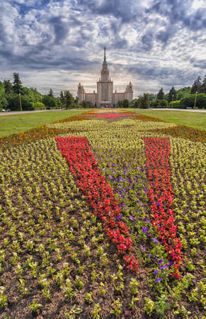 Moscow, Russia - June 15, 2020: the Moscow Lomonosov State University and the Wide flowerbed with flowers, vertical shot.