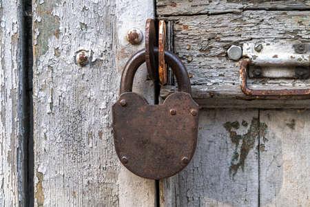 Old steel door lock on an old battered door, close-up. Stock fotó - 154772174