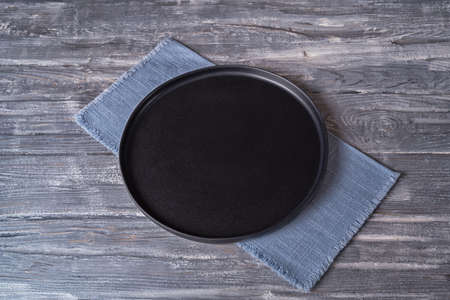 Black plate on blue napkin on gray wooden table, top view, place for a menu or recipe.