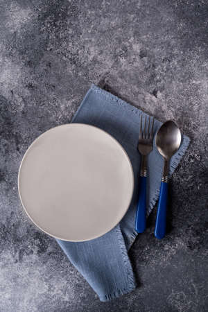 White plate on blue napkin on gray wooden table, top view, place for menu or recipe.