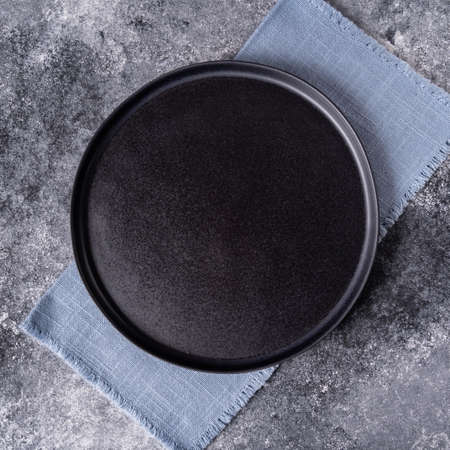 Black plate on a blue napkin on a wooden table, top view, place for a menu or recipe.