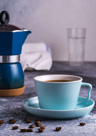 A cup of coffee and Geezer coffee maker under blurred bokeh background