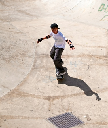Boy rides his skateboard . photo