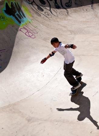 Boy rides his skateboard . photo