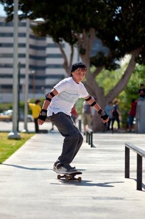 Boy rides his skateboard .