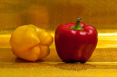 Yellow and red peppers on a golden background. photo