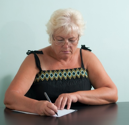 Mature woman with glasses writing a letter. photo