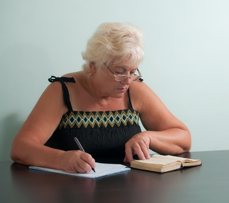 Mature woman with glasses writing . photo
