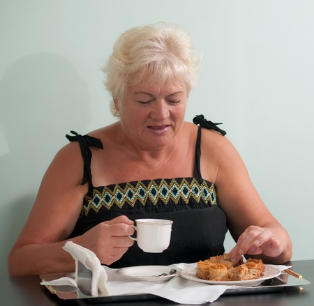 Portrait of friendly woman drinking tea with cookies . Stock Photo - 9554367