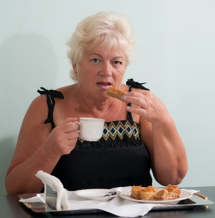 Portrait of friendly woman drinking tea with cookies . Stock Photo - 9554369