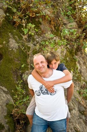 Man giving young boy piggyback ride outdoors smiling . Stock Photo - 9554547