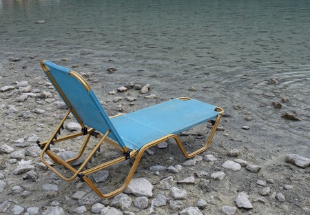 Chair on a shore of  lake . photo
