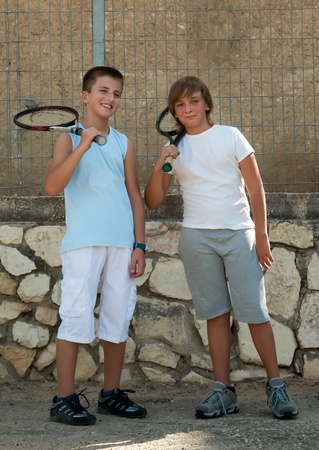 Two young male friends with rackets on tennis court smiling . photo