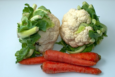 Freshly cut cauliflower cabbage and carrots  isolated on white .