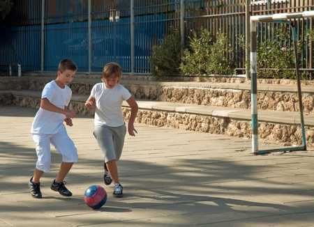 Teenage boys playing soccer at sunny day . photo