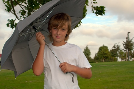Boy looking at camera while under umbrella outside  .