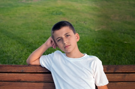 Boy sitting on a park bench with green meadow on the background . photo