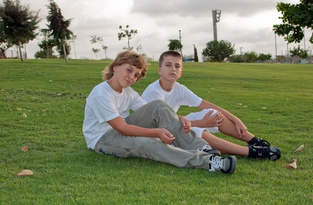 Portrait of two boys on the grass in the park  . photo