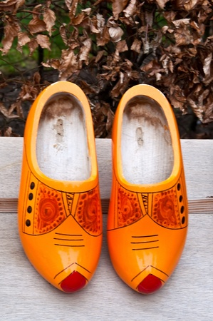 klompen: Pair of traditional Dutch  wooden shoes on a wooden table . Stock Photo