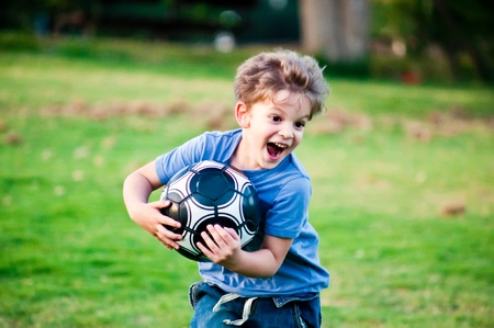 Cute little boy with a ball in a park . photo