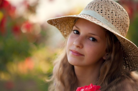 Portrait of teen girl in a straw hat against the backdrop of the garden. photo