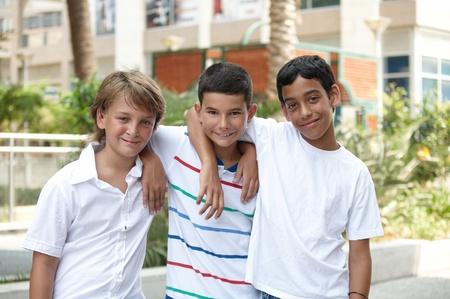 ni�os de diferentes razas: Retrato de tres hermosos ni�os sonrientes de distintas razas en el exterior. Foto de archivo