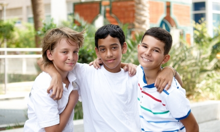 Portrait of three smiling handsome children of different races in outdoor . Stock Photo