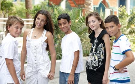 niños de diferentes razas: Retrato de cinco niños sonrientes guapos de diferentes razas en un natural al aire libre.