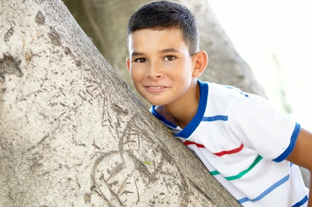 Portrait of a boy on the background of a tree trunk. photo