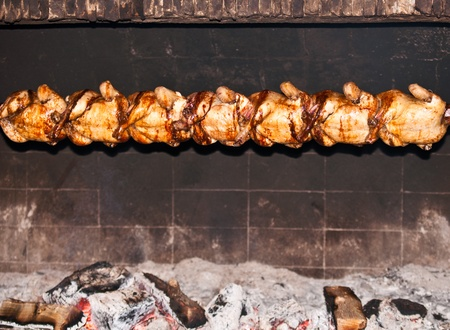 Chickens on grill on background of flames. photo