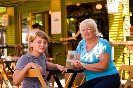 Boy with his grandmother in a cafe in outdoor restaurant on summer day . photo