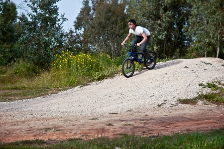 freeride: Teenager riding a bike on road through forest