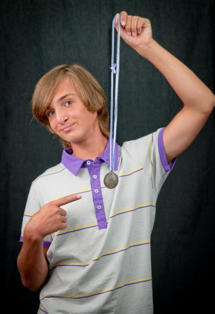 Portrait of a teenager boy   with a medal on a dark background . photo